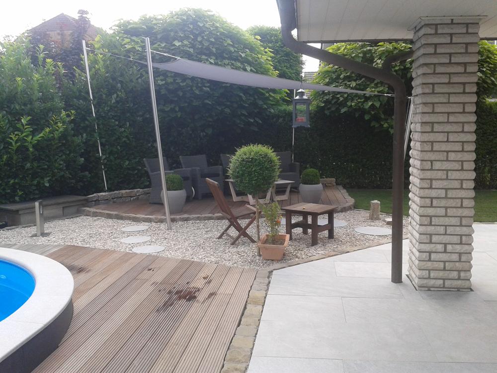 Gemütlicher Relaxbereich mit Kies und Holz am Pool